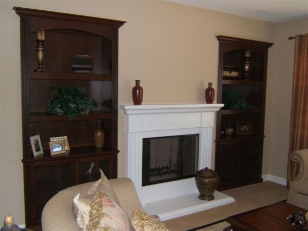 Custom cabinetry built into niches next to fireplace.