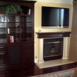 Wood fireplace mantel matches built in book shelves.