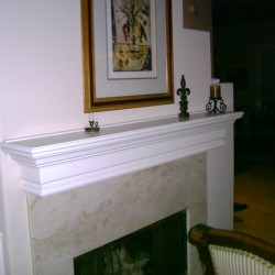 Wood fireplace mantel finished in white lacquer.