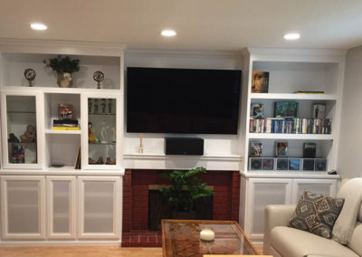 White wall unit built around fireplace.