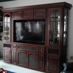 Built in entertainment center with glass and arched doors.