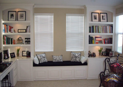 Built in white book shelves and window seat