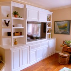 Built in entertainment center cabinets with white raised panel doors