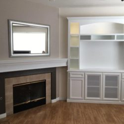 Custom entertainment center cabinets next to fireplace